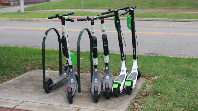 october 14 2018 lime scooters are left parked on the sidewalk along kirkwood avenue after being juiced in bloomington indiana several weeks ago... - motorino video stock e b–roll