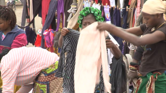 vídeos de stock e filmes b-roll de october 15 2010 ts locals with hair in rollers and scarves shoppings for clothes at a tent shop as another shopper buys a shirt with a few coins /... - moçambique