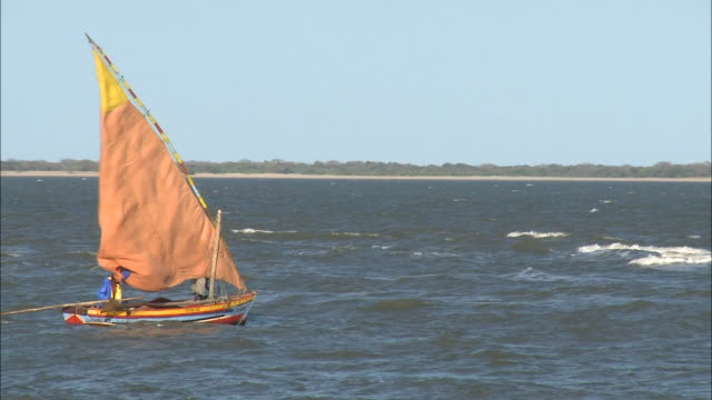 october 16, 2010 fishing boat rolling in offshore waves, big lateen sail flapping in gusting wind / mozambique - 大三角帆点の映像素材/bロール