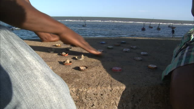 vídeos de stock e filmes b-roll de october 16, 2010 montage players playing game with bottle caps on flat stone, boats and ocean beyond / mozambique - enfoque de objeto sobre a mesa