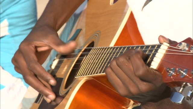october 16, 2010 musician playing guitar on beach, rolling waves beyond / mozambique - musician stock videos & royalty-free footage