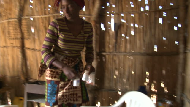 october 16, 2010 native pharmacist sorting pills in thatched hut / mozambique - tetto di paglia video stock e b–roll