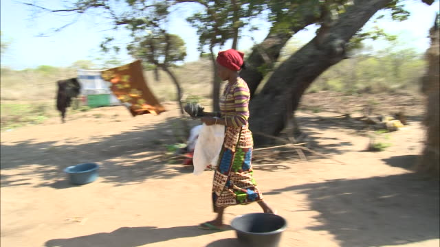 october 16, 2010 resident picking up raked debris outside thatched hut with her bare hands, laundry on the line beyond / mozambique - tetto di paglia video stock e b–roll