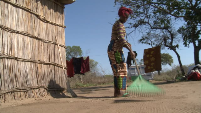 october 16, 2010 resident raking bare dirt yard with plastic rake outside thatched hut / mozambique - tetto di paglia video stock e b–roll