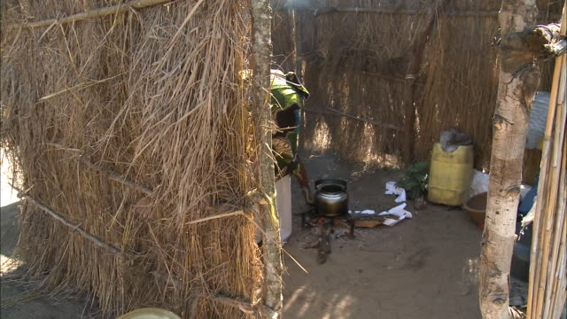 vídeos y material grabado en eventos de stock de october 16, 2010 resident starting smoky cooking fire inside thatched hut / mozambique - formato buzón