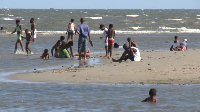 vidéos et rushes de october 16 2010 swimmers playing in the ocean waves and sitting in the sand / mozambique - format vignette
