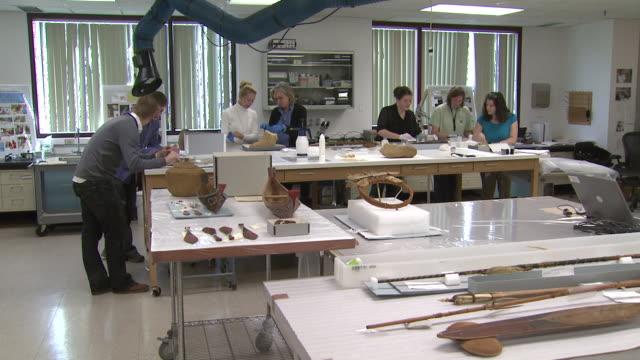 october 17, 2008 museum curators inspecting artifacts on tables / washington, d.c., united states - skåp med glasdörrar bildbanksvideor och videomaterial från bakom kulisserna
