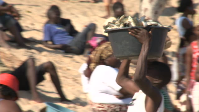 october 17 2010 ts child carrying bucket of fish on head and setting it on the beach / mozambique - unloading stock videos & royalty-free footage