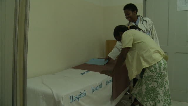 october 17 2010 ts doctor and patient walking from desk to examination table patient climbing up and lying down and doctor beginning exam / mozambique - examination table stock videos & royalty-free footage