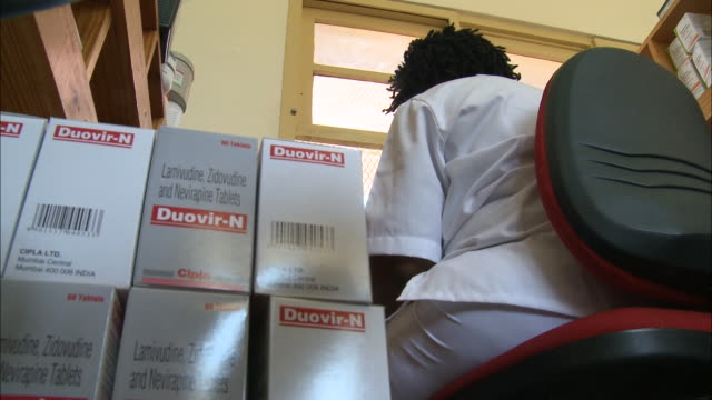 October 17 2010 LA Nurse sitting next to boxes of medicine used to treat HIV filling out paperwork at desk / Mozambique