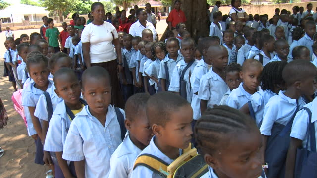 october 19 2010 pan elementary school students receiving instructions from their teacher during outdoor assembly / mozambique - reißschwenk stock-videos und b-roll-filmmaterial