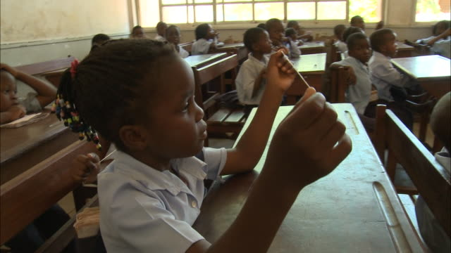 october 19 2010 pan elementary school students sitting at their desks holding a length of string as their teacher instructs them / mozambique - 分校点の映像素材/bロール