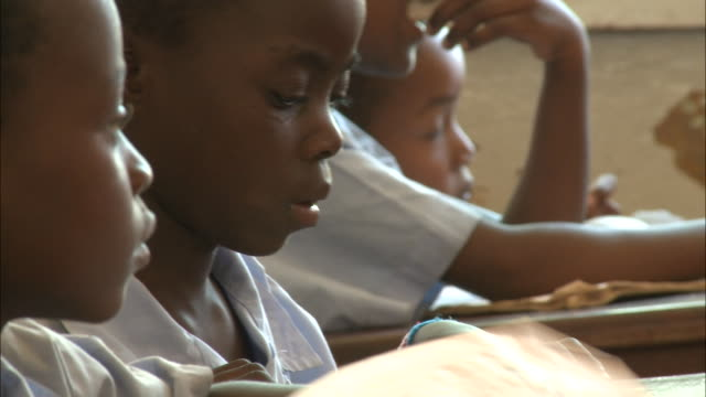october 19 2010 cu elementary school students sitting at their desks and writing in their workbooks during classroom lessons / mozambique - 分校点の映像素材/bロール