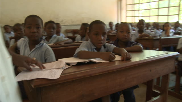 october 19 2010 pan elementary school students sitting at their desks paying attention to the teacher / mozambique - 分校点の映像素材/bロール