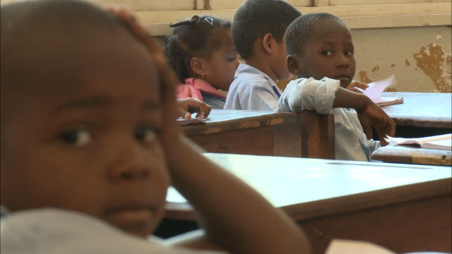 october 19 2010 ms elementary school students sitting distractedly at their desks during classroom lessons / mozambique - 分校点の映像素材/bロール