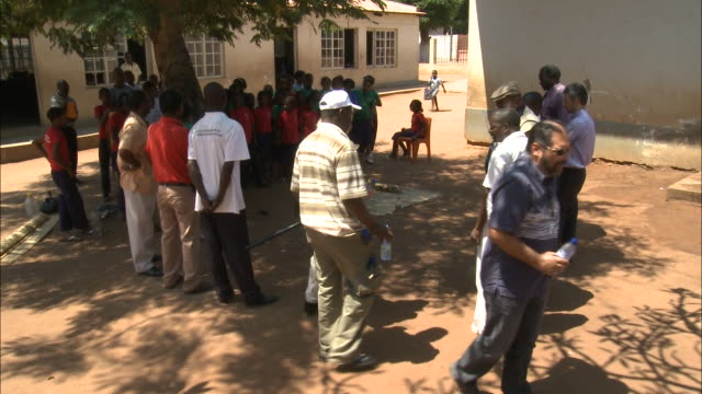october 19 2010 ws group of civic leaders and officials gathered outside the schoolhouse along with assembled students / mozambique - 分校点の映像素材/bロール