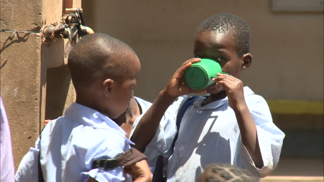 vidéos et rushes de october 19 2010 ms group of elementary school children gathered around outdoor water faucet alternately drinking from a cup and refilling it /... - eau potable