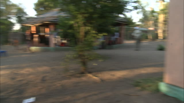october 19, 2010 round, open, thatched hut, and mural on wall warning of hiv / mozambique - レトロウィルス点の映像素材/bロール