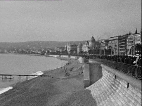 october 1936 b/w ws pan sea and promenade with hotels, pedestrians in warm clothing / cote d'azur, france - 1936 stock videos & royalty-free footage
