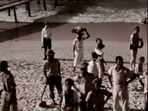 vidéos et rushes de october 1936 ws pan ha locals and westerners on beach / west indies - antilles occidentales