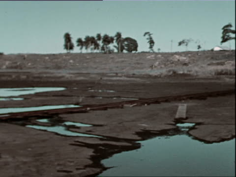 vidéos et rushes de october 1936 montage construction site, lady and gentleman in white outfit and hat talking, workers digging ditches on ground with hoe / west indies - antilles occidentales
