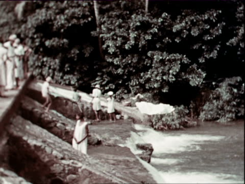 vidéos et rushes de october 1936 montage local women washing clothes by river dam, kids playing in water, western lady and gentleman in white tropical outfit standing next to car by dam / west indies - antilles occidentales
