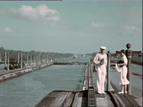 october 1936 montage panama canal: lady and gentleman in white outfits standing by canal / panama - panamakanal stock-videos und b-roll-filmmaterial