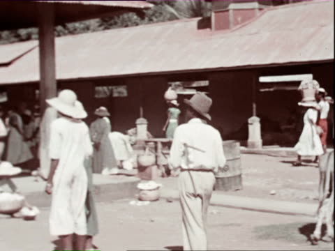 October 1936 MONTAGE Town market, vendors selling fruits and vegetables in open air market, two men walking past parked car holding pig / West Indies