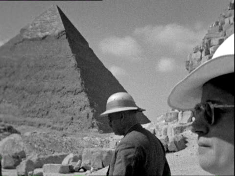 October 1938 B/W MONTAGE Giza Pyramids, Western tourists in hat, sunglasses and tropical gear on camel backs being led by Egyptian guides / Egypt