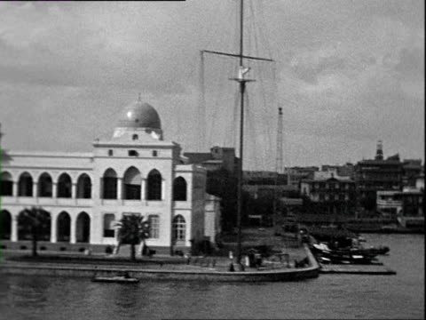 october 1938 b/w montage moving on canal with moored ships, simon arzt cigarette factory, statue of ferdinand de lesseps at entrance to suez canal / port said, egypt - suez canal stock videos & royalty-free footage