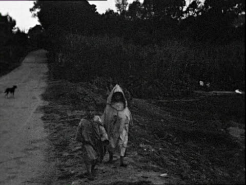 october 1938 b/w montage poor children in slums near creek, goats in background / algiers, algeria - アルジェリア点の映像素材/bロール