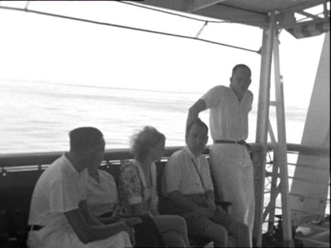 october 1938 b/w ws pan passengers relaxing on deck of ocean liner / red sea - 船の一部点の映像素材/bロール
