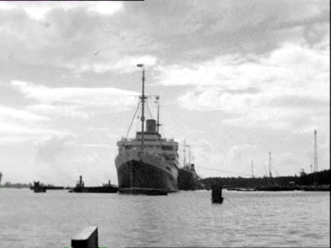 october 1938 b/w pov passing big moored ocean liners and small boats - 客船点の映像素材/bロール