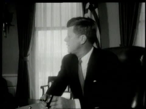 October 1962 MS John F Kennedy sitting at desk in Oval Office / Washington DC United States