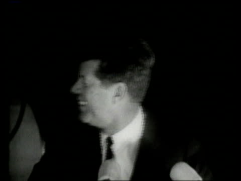 october 1962 montage john f. kennedy smiling and speaking to huge crowd at night, audience applauding him / new haven, connecticut, united states - 1962年点の映像素材/bロール