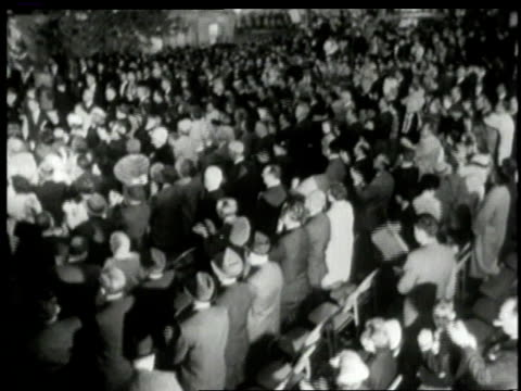 October 1962 MONTAGE John F Kennedy smiling and speaking to huge crowd at night audience applauding him / New Haven Connecticut United States