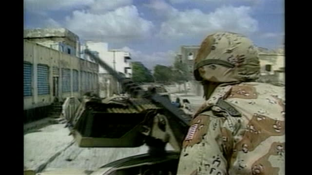 October 1993 US troops on patrol in military vehicles through ruins US Black Hawk helicopters landing
