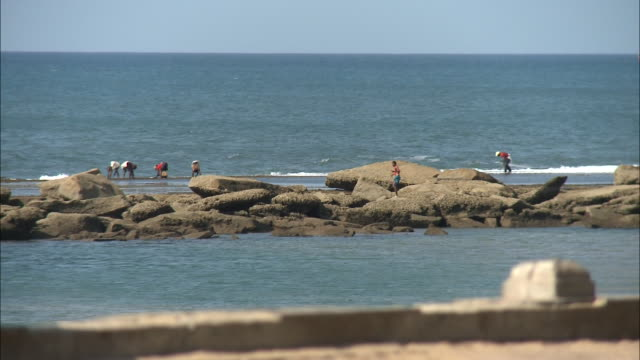 October 20 2010 R/F Beachcombers standing on offshore rocks and remains of elegant Portuguese columns on sandy beach / Mozambique