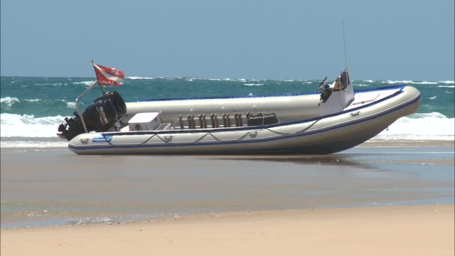 october 20, 2010 beached motorboat near ocean waves / mozambique - stationary process plate stock videos & royalty-free footage