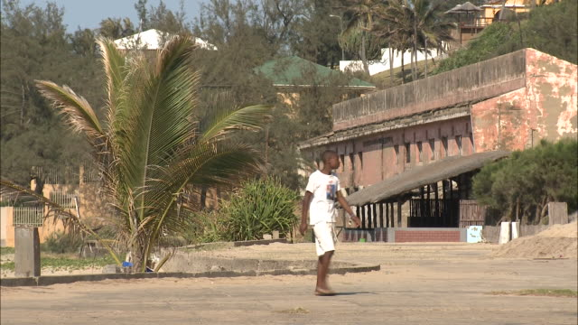 October 20 2010 LA Pedestrian passing by old Portuguese colonial building and palm trees / Mozambique