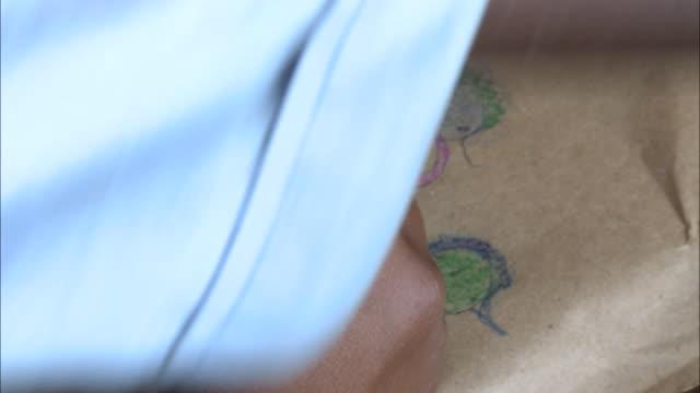 october 20 2010 ha student drawing blue and green figures at desk with colored pencils / mozambique - bordsyteinspelning bildbanksvideor och videomaterial från bakom kulisserna
