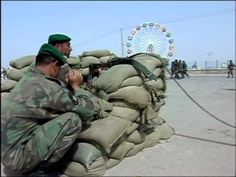 vídeos de stock e filmes b-roll de october 2004 afghan national army soldiers on guard behind sandbags across street from ferris wheel as ana troops leave for joint patrol with... - kandahar