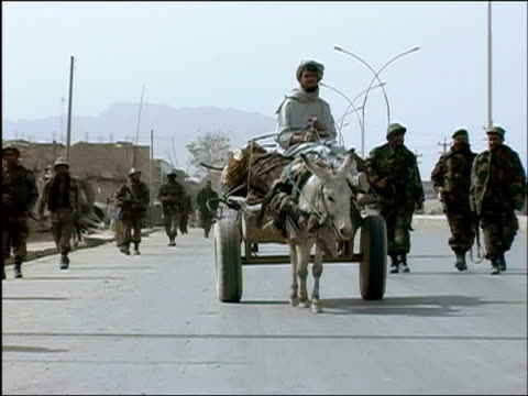 october 2004 afghan national army troops on usled joint patrol with romanian embedded training team walking past man riding muledrawn cart and... - 荷車点の映像素材/bロール