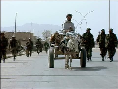 october 2004 afghan national army troops on usled joint patrol with romanian embedded training team walking past man riding muledrawn cart and... - hästkärra bildbanksvideor och videomaterial från bakom kulisserna