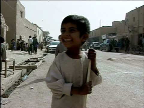 stockvideo's en b-roll-footage met october 2004 boy holding hand out to soldiers from afghan national army and romanian embedded training team on joint patrol in days leading up to... - kandahar afghanistan