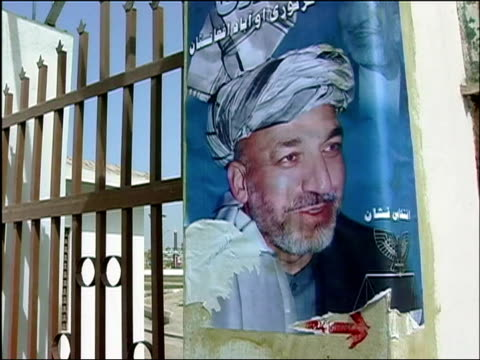 october 2004 campaign poster for hamid karzai on gate in days leading up to first national election / kandahar, afghanistan / audio - 2004 stock videos & royalty-free footage