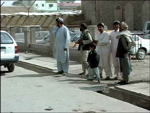 vídeos de stock e filmes b-roll de october 2004 civilians waiting to cross street as troops from afghan national army and romanian embedded training team on joint patrol walk by in... - kandahar