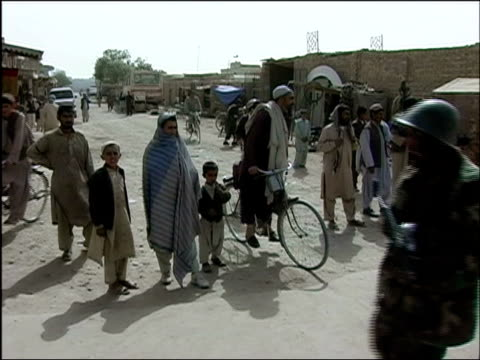 vídeos de stock e filmes b-roll de october 2004 civilians watching joint patrol of troops from afghan national army and romanian embedded training team walk by on street in days... - kandahar