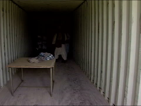 October 2004 Men loading ballot boxes into cargo container at Kandahar Stadium in days immediately following presidential election / Kandahar...
