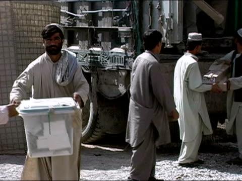 vídeos de stock e filmes b-roll de october 2004 men passing ballot boxes down line from truck parked at kandahar stadium as ballots start to arrive in days immediately following... - kandahar